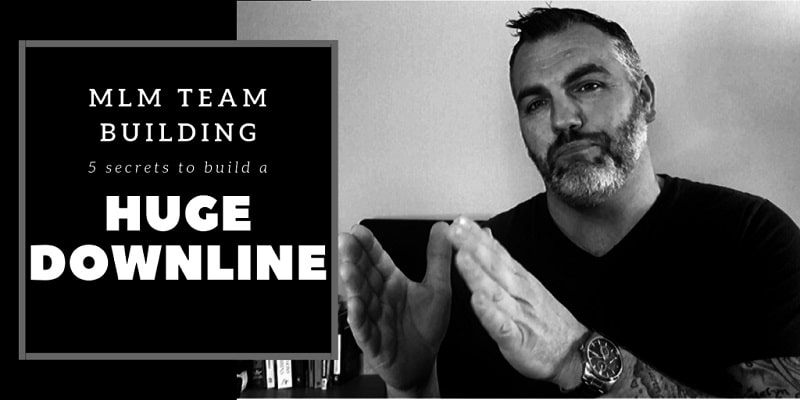 """An image with two section to it. The section on the right is a photo of a man with a silver watch on, wearing a black shirt and has a salt and pepper beard, sitting at his office desk. The section on the left is text that says: """"MLM team building""""."""
