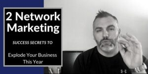 """On the left is a text box with the words """"network marketing success secrets"""". On the right is a black and white photo of a man wearing a black shirt sitting in front of his computer looking at the camera."""