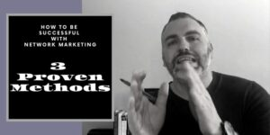 """Guy wearing a black t-shirt, with a black watch on this left arm and a pen in his right hand. It looks like he is talking. There are words written on the photo that say """"how to be successful with network marketing""""."""