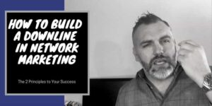 A guy in front of a black computer with his hand raised as he is talking, the words how to build a downline in network marketing are typed on the screen