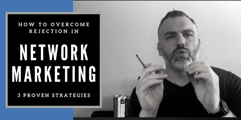 """a business trainer doing a training video, both of his hands are raaised in front of his face and a pen is in his left hand. The words """"how to overcome rejection in network marketing"""" is in a frame to the left of the trainer."""