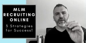 """A man sitting at his desk at his home office facing away from his computer monitor. He has his hand up like he is making a point. There is text on the side of the blog that reads """"MLM Recruiting Online""""."""