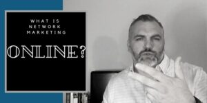 """Mr. Corbett wearing a dress shirt, with his hair slicked back, he is holding two fingers of his left hand up. The Title of the picture reads """"what is network marketing online?"""""""