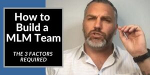 A dude wearing a white shit, collar is open, he has a grey bear and is holding up his left hand. The words how to build a mlm team are typed to the left of him.