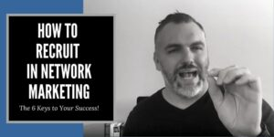 A fella in a black shirt sitting at his desk, there is a tony robbins book behind him and a computer monitor can be seen over his right shoulder. The words how to recruit in network marketing are written in the left corner of the photo.