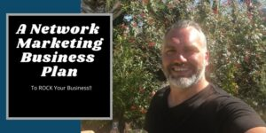 """Robb standing in front of a rose bush in a park in Seminole Florida, his face is red from the sun. The heading on the photo says """"network marketing business plan""""."""