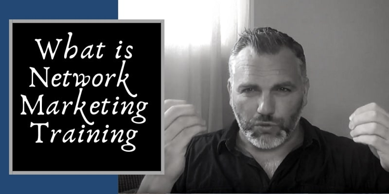 """Robb wearing a blue denim shirt sitting on his couch, rocking a great hair cut and nicely trimmed beard talking about """"what is network marketing training"""", which is also pasted onto the picture to the left of his arm."""