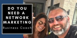A man and a woman wearing sun glasses, sitting out in the sun on a patio taking a selfie. On the phone next to them the following words are written: do you need a network marketing business coach.