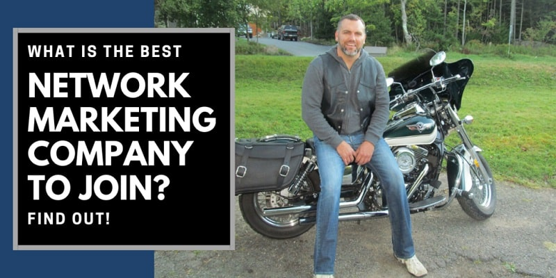 Robb Corbett leaning against his motor cycle. Next to him on his right side are the words: What is the best network marketing company.