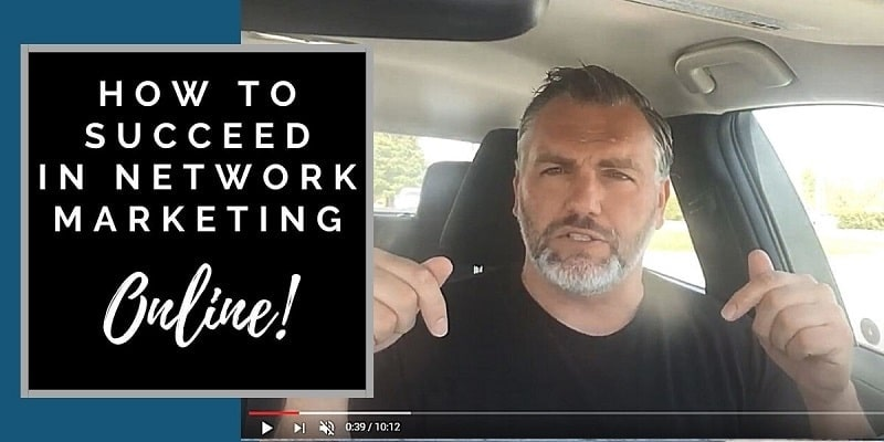 """A man in the front seat of his car parked, he is wearing a black shirt and pointing down. The works """"how to succeed in network marketing"""" are also on the picture to the left of the man."""