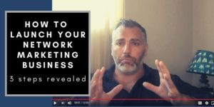 """A guy with great hair sitting on a couch with a lamp behind him that has a shade with sail boats on it. The words """"how to launch your network marketing business"""" are on the screen next to the guy."""