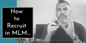 a man with both hands raised p to his face wearing a black shirt with a silver watch and the words how to recruit in mlm are written on the left side of the image