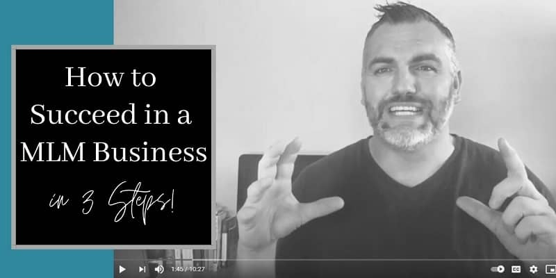Man with hands raised like he is training people. Sitting in front of a computer. There are books next to him on the desk. The words how to succeed in a mlm business are written on the picture to the left.