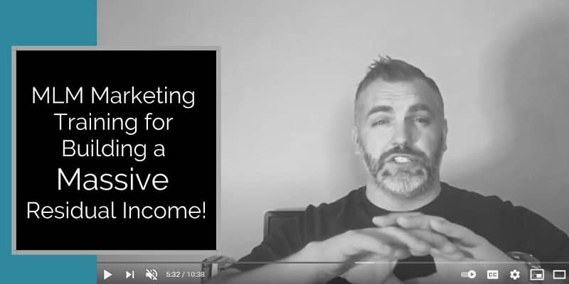 guy with his two hands clasped together in front of him, wearing a black shirt, and smiling. MLM Marketing training is typed on the photo to the right of the man.