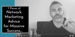 man in his office sitting with his back to his computer monitor wearing a black shirt and a silver watch with his index finger raised and the words 7 pieces of network marketing advice written on the image