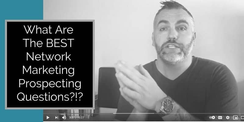 A guy facing the camera with his back to his desk, his hands are clasped together and the works what are the best network marketing prospecting questions are typed on the picture