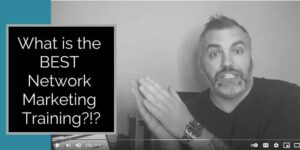 black and white photo of a guy facing the camera with his hands clasped together wearing a black sweater wearing a big watch and words what is the best network marketing training written to the right of the man