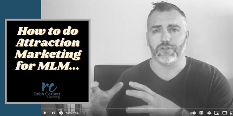 """a great looking man with a salt and pepper beard wearing a navy blue shirt sitting with his back to his desk. The title on the phone reads """"attraction marketing for MLM""""."""