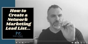 a male speaking into a camera wearing a nice black shirt, and a salt and pepper beard short beard and hair slicked back sitting at his office desk. The title on the photo reads how to create a network marketing lead list.