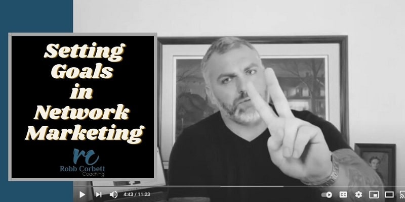 a black and white photo of a man in a black shirt sitting in front of a painting of a farm giving the peace sign. The title of the phone is setting goals in network marketing.