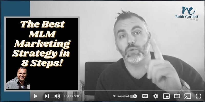 Mr Corbett sitting down with his back to his computer, his left index finger is raised and the words the best mlm marketing strategy are written next to him.