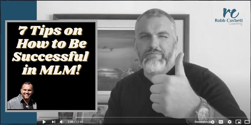 A man in a black sweater sitting at a high table winking and giving a thumbs up. The title on the photo is: how to be successful in mlm.