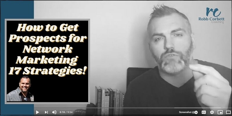 A dude facing the camera with his back to his desk, there are success books on the desk, he has is left hand raised pointing and the following words are written on the photo: how to get prospects for network marketing.