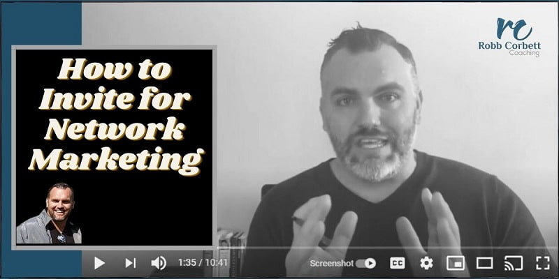 Tall man sitting with his back to the wall. He is speaking into the camera with his hands raised and a pen in his left hang. The title of the photo reads how to invite for network marketing.