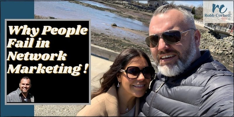 A couple standing on a pier with the ocean and a little village in the back ground. The words why people fail in network marketing are typed on the photo.
